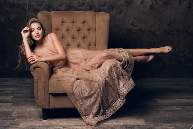 Mooie sexy modelvrouw in glanzende kanten avondjurk poseren zittend in stoel van beige kleur