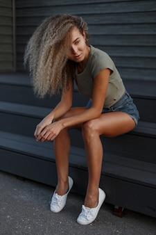 Mooie sexy modieuze krullende modelvrouw met mooie benen in jeansborrels die op de treden zitten