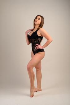 Mooie sexy mollige lichaam van de vrouw in de studio met tatoeages. vrouwelijk studioportret, zwarte bodysuit