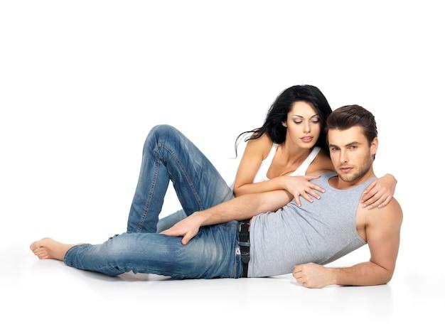 Mooie sexy paar verliefd op witte ruimte gekleed in blauwe jeanse en wit onderhemd