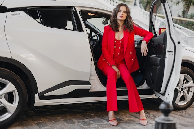 Mooie sexy rijke zakenvrouw in rood pak poseren in witte auto