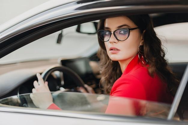 Mooie sexy rijke zakenvrouw in rood pak rijden in witte auto, bril, zakelijke dame stijl