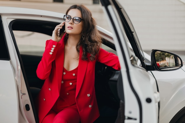 Mooie sexy rijke zakenvrouw in rood pak zit in witte auto, bril praten over de telefoon, zakelijke dame stijl