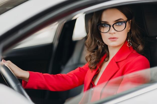 Mooie sexy rijke zakenvrouw in rood pak zit in witte auto, bril
