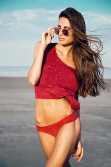 Mooie sexy slanke vrouw in rode bikini en t-shirt met een bril poseren op het strand tegen een blauwe hemel. zomerstemming.