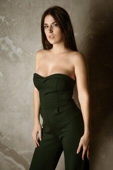 Mooie sexy vrouw die in groen kostuum de camera bekijkt