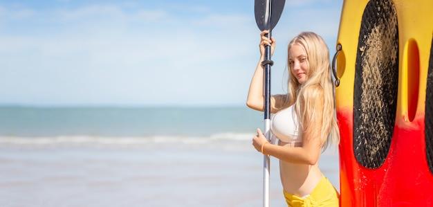 Mooie sexy vrouw die zich met peddel door kajakboot bevindt op het strand in de blauwe zee van andaman en de blauwe hemel.
