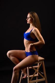 Mooie sexy vrouw in blauw ondergoed op een donkere achtergrond, perfect vrouwelijk lichaam, studio-opname
