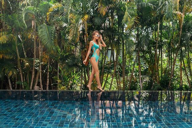 Mooie sexy vrouw in blauwe bikini die zich dichtbij zwembad bevindt.