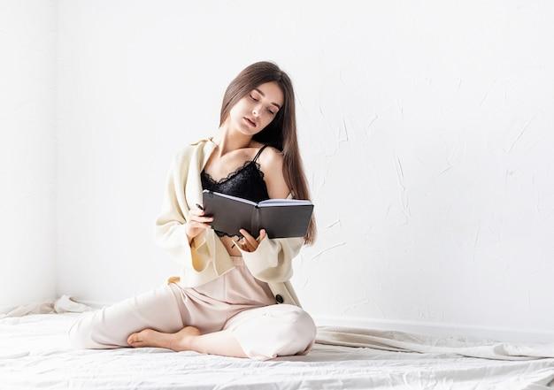 Mooie sexy vrouw in comfortabele huiskleren schrijven van notities zittend op de vloer, denken