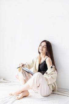 Mooie sexy vrouw in comfortabele huiskleren schrijven van notities zittend op de vloer, dromen met gesloten ogen