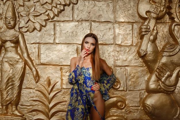 Mooie sexy vrouw in designer zwembroek in de buurt van de gouden muur