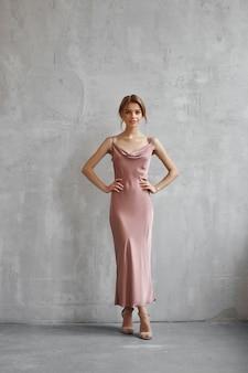 Mooie sexy vrouw in een licht beige zijden jurk. ruis, onscherp