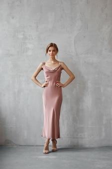 Mooie sexy vrouw in een licht beige zijden jurk