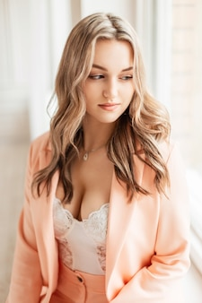 Mooie sexy vrouw in een modieuze blazer en witte bodysuit zit thuis bij het raam