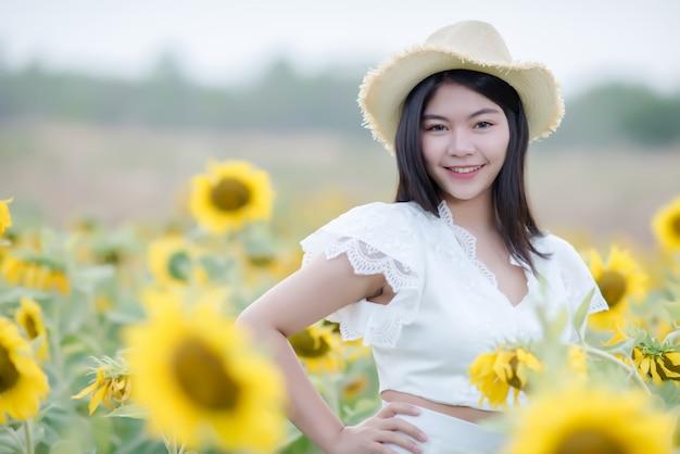 Mooie sexy vrouw in een witte jurk lopen op een veld met zonnebloemen