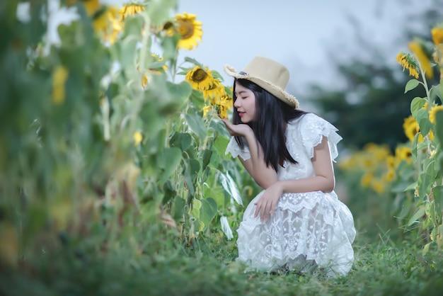 Mooie sexy vrouw in een witte jurk op een veld met zonnebloemen, gezonde levensstijl