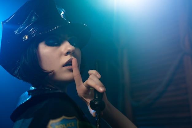Mooie sexy vrouw in erotische kleding politie kostuum voor bdsm overheersing in de stralen van licht en rook