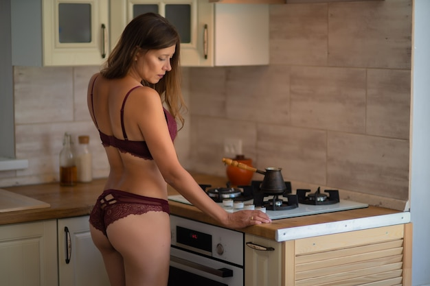 Mooie sexy vrouw in lingerie in de keuken thuis