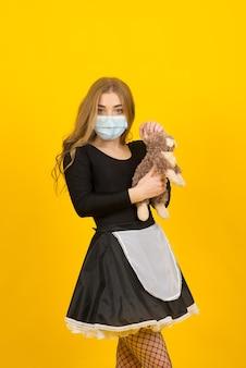 Mooie sexy vrouw in meid kleren poseren met konijn speelgoed in covid beschermend masker