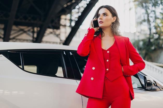 Mooie sexy vrouw in rood pak poseren bij auto praten over zaken op telefoon