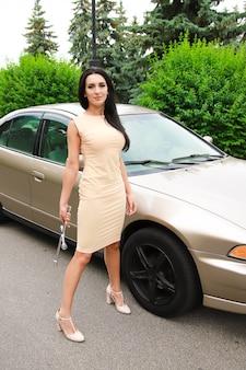Mooie sexy vrouw met donker haar op een achtergrond van een auto met een moersleutel