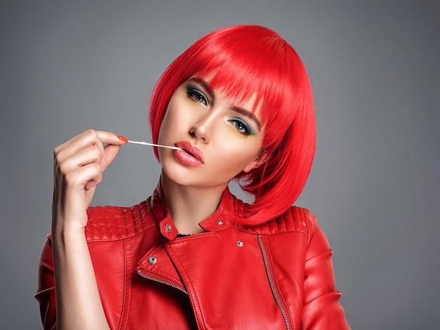 Mooie sexy vrouw met helder rood bobkapsel. model. sensueel prachtig meisje in een leren jas. prachtig gezicht van een mooie dame. slimme meid strekt zich uit kauwgom