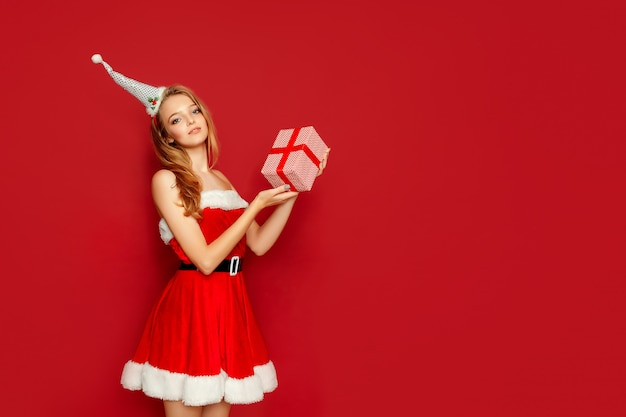 Mooie sexy vrouw met santa claus-kostuum en gift