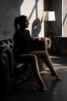 Mooie sexy vrouw op leerbank in donkere kamer