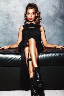 Mooie sexy vrouwen modeldame met rode lippen in zwarte elegante kledingszitting op bank dichtbij grijze muur