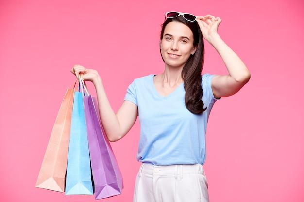 Mooie shopper in t-shirt, broek en zonnebril geïsoleerd op roze muur
