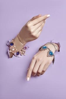 Mooie sieraden op handen van vrouwen, gescheurd papier