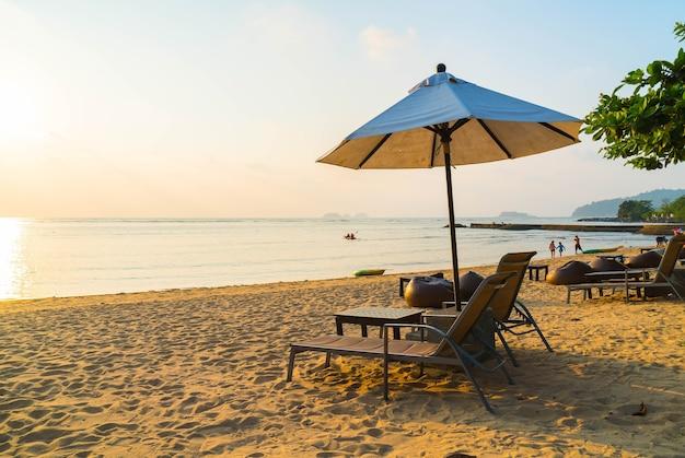 Mooie silhouette luxe paraplu en stoel rond zwembad in hotel zwembad resort met kokospalm bij zonsopgang tijden