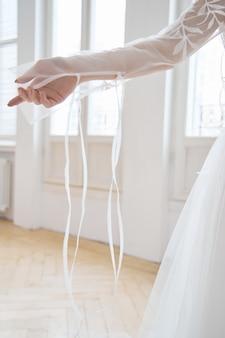 Mooie slanke blonde in de avondzon in een lange witte jurk bij een groot raam. perfect haar en make-up voor de bruid, een nieuwe collectie trouwjurken