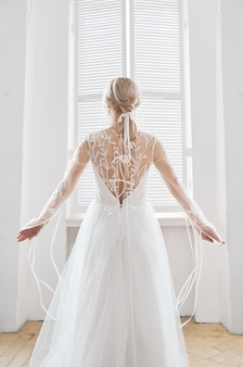 Mooie slanke blonde in de avondzon in een lange witte jurk in de buurt van een groot raam. perfect haar en make-up voor de bruid, een nieuwe collectie trouwjurken