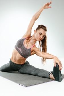 Mooie slanke brunette doet wat rekoefeningen in een sportschool