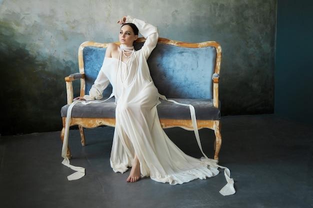 Mooie slanke brunette meisje zittend op de bank in een lange witte jurk. portret van een vrouw met een sieraad om de nek. perfect kapsel en cosmetica van de vrouw, nieuwe collectie lichte jurken