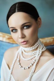 Mooie slanke brunette meisje, zittend op de bank in lange witte jurk. portretvrouw met juwelen op hals.