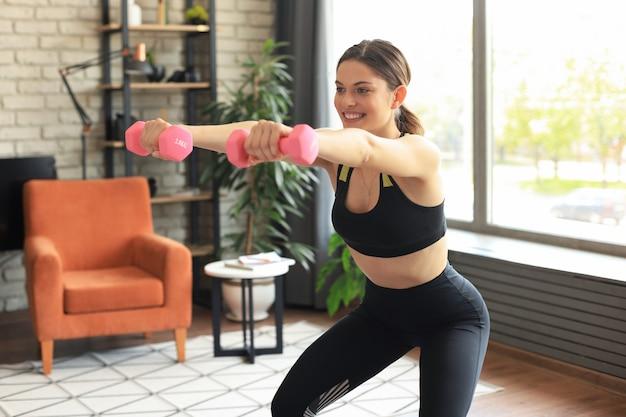 Mooie slanke fitness vrouw hurkt met halters. sporten, gezonde levensstijl. meisje gaat thuis sporten.