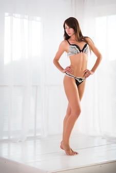 Mooie slanke jonge brunette vrouw in zwart-wit sexy ondergoed staande op witte vloer op witte achtergrond.