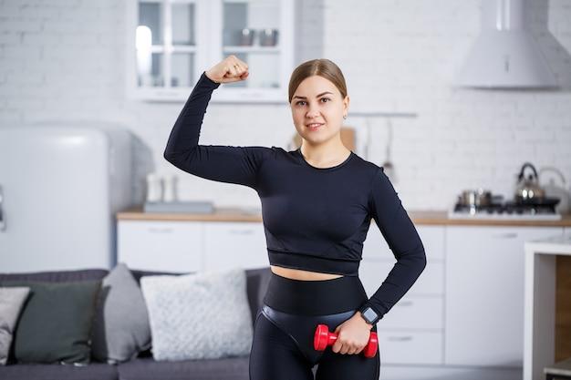 Mooie slanke jonge vrouw gaat thuis sporten in een top en legging. thuis fitnessen voor een mooi lichaam. oefeningen met halters voor het vrouwelijk lichaam. gezonde levensstijl.