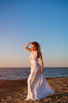 Mooie slanke jonge vrouw van blanke etniciteit met lang haar staat in een witte jurk in de w...
