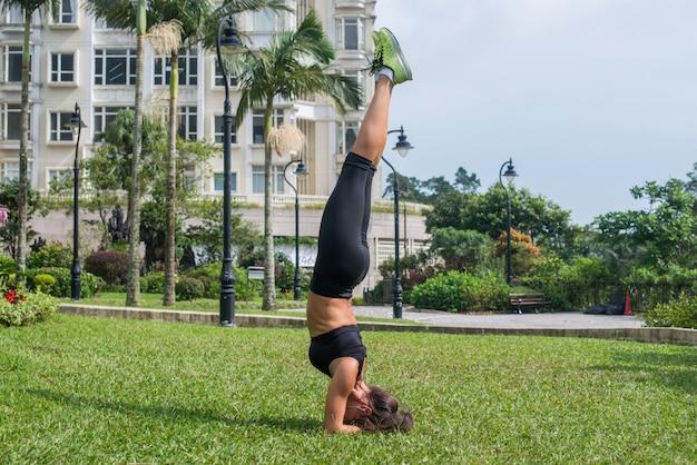 Mooie slanke sportieve jonge vrouw die handstand of ondersteunde headstandoefening in openlucht doet. fitness meisje beoefenen van yoga houding in park
