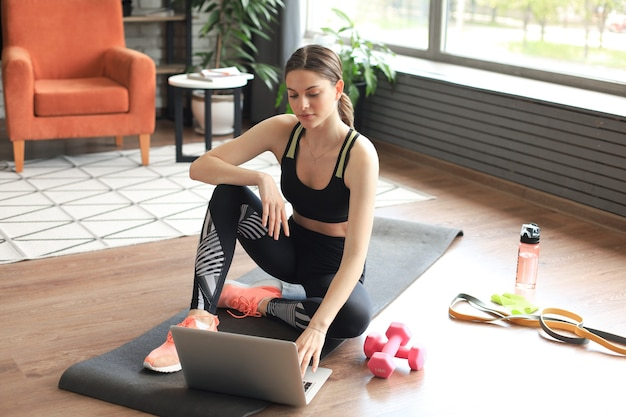 Mooie slanke sportieve vrouw in sportkleding zit op de grond met halters en een fles water en gebruikt een laptop thuis in de woonkamer. gezonde levensstijl. blijf thuis activiteiten.