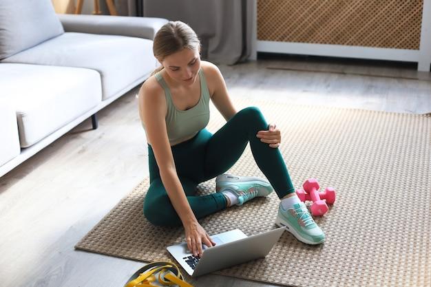 Mooie slanke sportieve vrouw in sportkleding zit op de grond met halters en gebruikt een laptop thuis in de woonkamer. gezonde levensstijl. blijf thuis activiteiten.