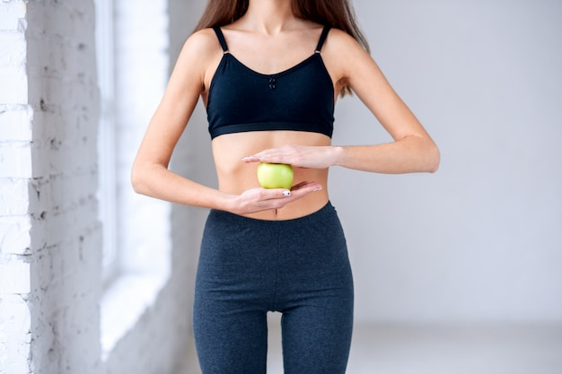 Mooie slanke vrouw die in donkere sportwear groene appel in de handen houdt dichtbij haar aantrekkelijke buik