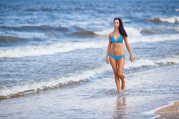 Mooie slanke vrouw in een blauw zwempak die op het strand lopen