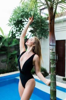 Mooie slanke vrouw in open witte zwembroek staat in het zwembad in tropisch resort