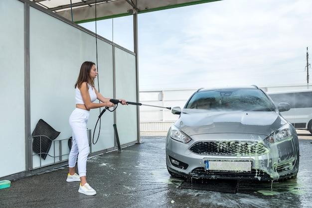 Mooie slanke vrouw maakt haar auto schoon in een wasstraat met waterpistool