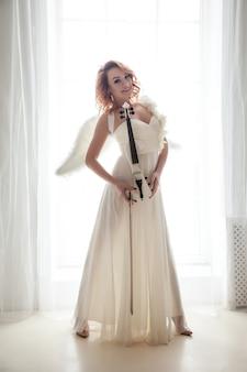 Mooie, slanke vrouw met viool en vleugels